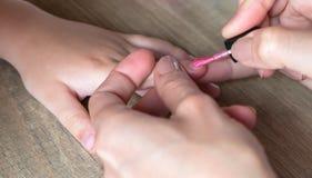 Hands of a woman who puts a pink nail polish stock photos