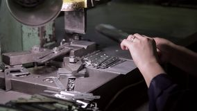 Hands of a woman working in the factory and stamping metal products stock video footage