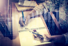 Hands of woman working on office desk. Hands of woman working on office desk which one hand holding a smart phone and writing on notepad with virtual graphic Royalty Free Stock Images