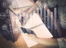 Hands of woman working on office desk. Which one hand holding a smart phone and writing on notepad with virtual graphic icon diagram Royalty Free Stock Photography