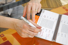 Hands of woman by writing in a calendar Royalty Free Stock Photo