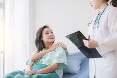 Hands woman doctor reassuring her female asian patient in hospital room,Doctor giving a consultation and encouragement to patient royalty free stock image