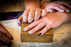 Getting married. Hands of 2 women getting married hold on top of each other on the top of little wooden box with a book underneath Stock Photo