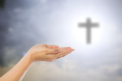 Hands of women praying over blurred the cross on the sky backgro Royalty Free Stock Image