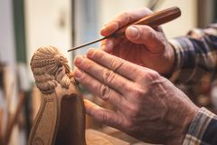 Hands of a wood sculptor working on a small wooden figure royalty free stock images