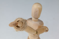 Hands of wooden figurine tied with a rope Royalty Free Stock Photos