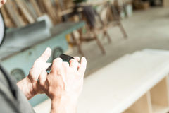 Hands of a woodworker using a mobile Royalty Free Stock Photos
