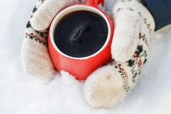 Hands in woolen mittens hold a red mug with hot tea or coffee, standing on the snow. Concept of warming on a winter walk stock image