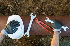 Hands with work gloves holding a safety helmet, a wrench and a red key pipe clamps Stock Photography