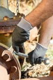 Hands with Work Gloves Holding a Wrench and Tighten very Rusty Bolts Stock Images