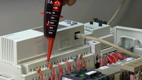 Hands of worker check contacts voltage indicator in electronics in factory. Handwork processes. Manufactory energy measurement accuracy technology. Computer stock video footage