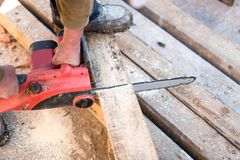 Hands of worker cutting wooden boards on contruction site with electric circular saw Stock Photos