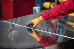 The hands of the worker measure the size of metal with a tape measure.  Royalty Free Stock Photos