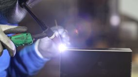 Hands of worker welding in factory stock footage
