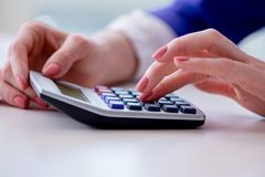 The hands working on accounting calculator calculating profit. Hands working on accounting calculator calculating profit Stock Photo