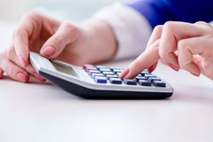 The hands working on accounting calculator calculating profit. Hands working on accounting calculator calculating profit Stock Image