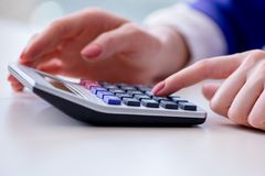 The hands working on accounting calculator calculating profit. Hands working on accounting calculator calculating profit Royalty Free Stock Images