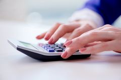 The hands working on accounting calculator calculating profit. Hands working on accounting calculator calculating profit Royalty Free Stock Photos