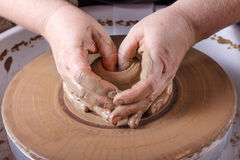 Hands working with clay on potter's wheel. Stock Photography