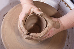 Hands working with clay on potter's wheel. Royalty Free Stock Photo