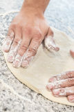 Hands working dough. Floured hands working fresh pizza dough Stock Photo