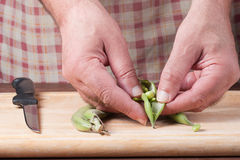 Hands working in the kitchen. Preparing the beans to be cooked, a knife nearby Royalty Free Stock Photos