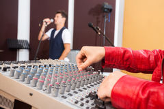 Hands Working On Music Mixer While Man Singing Stock Photo