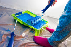 Hands working with painting roller. Girl painting with blue painting roller brush and green pallet stock photo