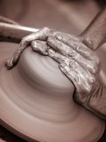 Hands working on pottery wheel ,  artistic  toned Stock Photography