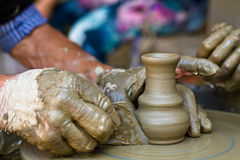 Hands working on pottery wheel , close up Stock Photo