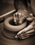 Hands working on pottery wheel. Close up retro style toned photo wit shallow DOF Royalty Free Stock Photography