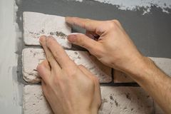 Hands working tiler in the process of laying plaster tiles on the wall of the room. Repair of apartments stock photography
