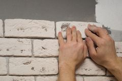 Hands working tiler in the process of laying plaster tiles on the wall of the room. Repair of apartments royalty free stock photography