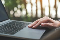 Hands working , touching and typing on laptop keyboard with blur nature background Royalty Free Stock Images