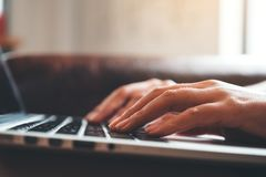 Hands working and typing on laptop keyboard on wooden table with blur background. Closeup image of hands working and typing on laptop keyboard on wooden table royalty free stock images