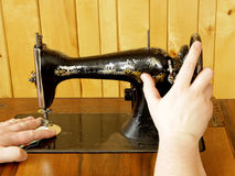 Hands working with vintage mechanical sewing machine. Closeup royalty free stock images