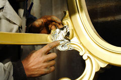 Hands working on wood gilding. Hands working on wood with gold film Royalty Free Stock Photo