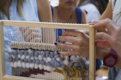 Vertical loom weaving hands working blue yellow wool royalty free stock photo