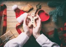 Hands wrapping christmas gingerbread man cookies Stock Photo