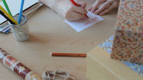 Hands write a greeting card and put it into a present box stock video footage