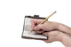 Hands write a pencil in your notebook Stock Photography