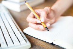 Hands writes a pen in a notebook. Stock Photos