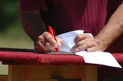 Hands writing. White writing hands of a caucasian architect making notes with a red pen on paper outdoors Stock Image