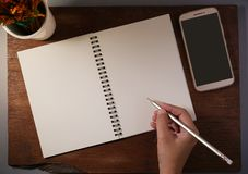 Hands writing in blank notebook by pencil with black screen smartphone. royalty free stock image