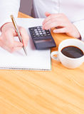 Hands writing with coffee and calculator, planning Stock Image