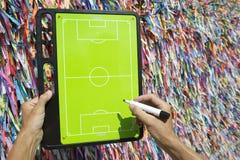 Hands Writing on Football Tactics Board Wish Ribbons Brazil. Hands writing on football tactics board in front of Brazilian wish ribbons in Salvador Bahia Brazil Royalty Free Stock Image
