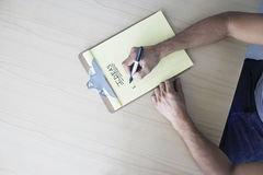 Hands Writing 'Ideas' On Clipboard Stock Photography