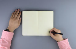 Hands writing in the note book. Flat lay style Royalty Free Stock Photos
