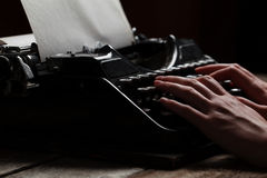 Hands writing on old typewriter over wooden table Stock Image