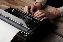 Hands writing on old typewriter over wooden table Stock Photo